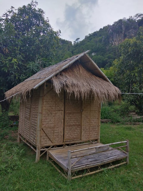 Bamboo bungalow in the middle of the bay, mountains, forest cover.