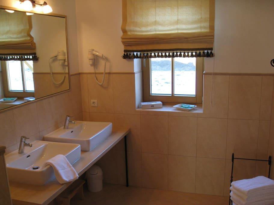 Badezimmer mit Doppelwaschbecken und Dusche. Toilette ist separat