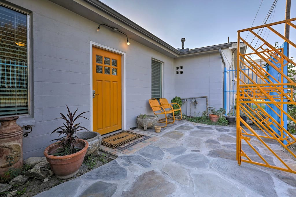 A stone patio and canary yellow features welcome you to the property.
