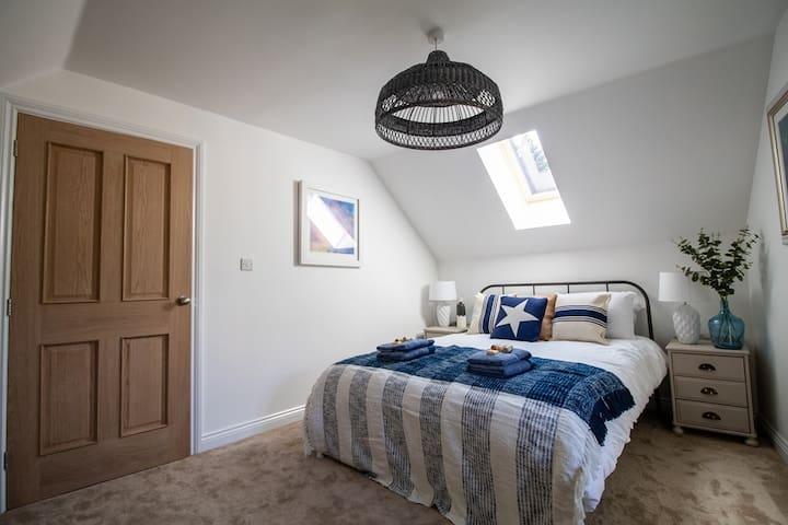Bedroom with King Size Bed. Door to upstairs landing.