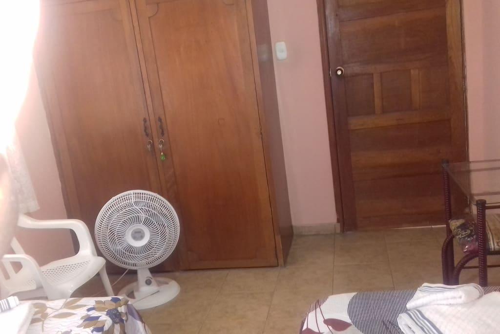 Dos camas sencillas, silla, abanico, closet, tocador con espejo y puf. puerta con seguro.