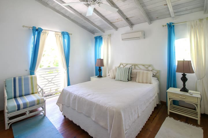 The second bedroom with air-conditioning and views overlooking the pool and garden
