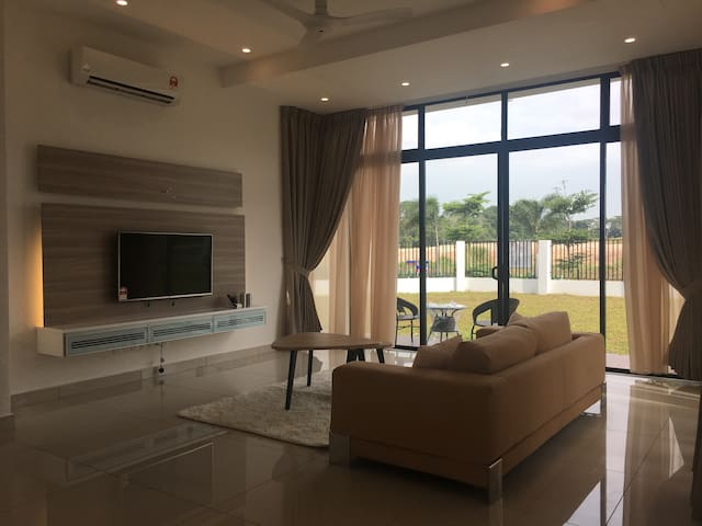 """Living Room - Large Super comfy sofa with 50"""" LED TV on feature wall. external patio with cozy chairs and side table outdoor"""