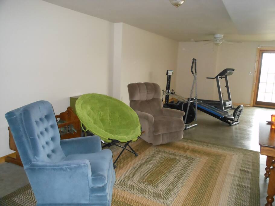 Sitting area with treadmill and elliptical.