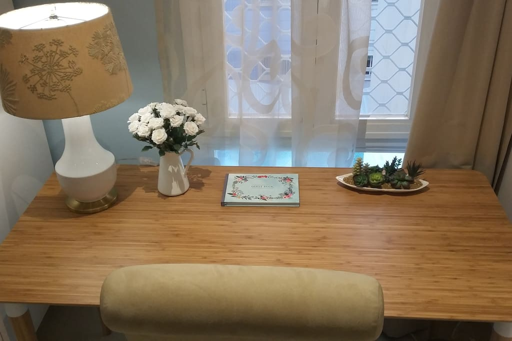 Bamboo desk with guest book, table lamp, flowers/cacti
