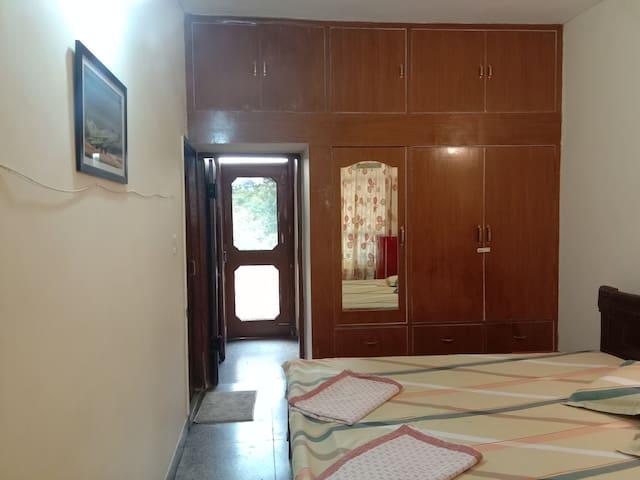 Bedroom 1 as seen from living room door. Kitchen entrance door is open and balcony is behind wire mesh door.