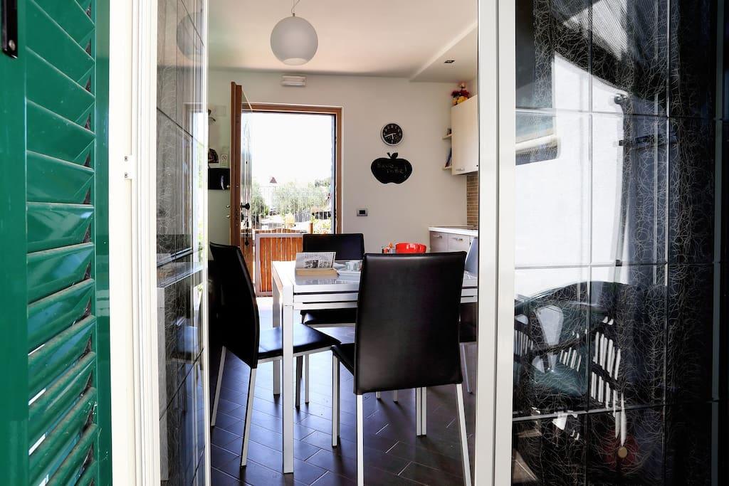dalla veranda si vede l'interno del soggiorno e l'entrata sulla strada col cancelletto di legno