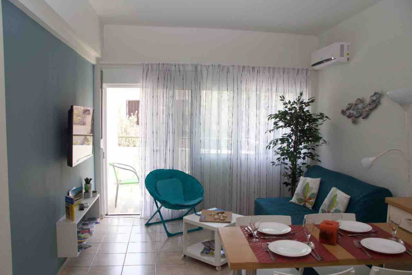 Sitting room of this fully air conditioned one bedroom apartment with open kitchen.  The large window leads  to one of the balconies.