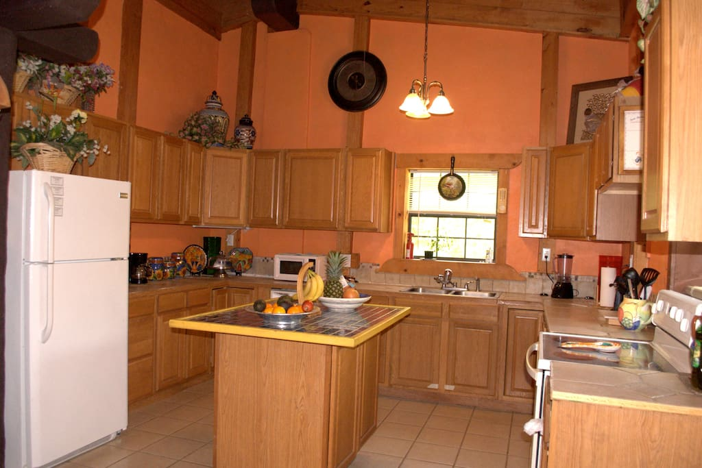 Kitchen with microwave, electric stove, coffee maker and blender