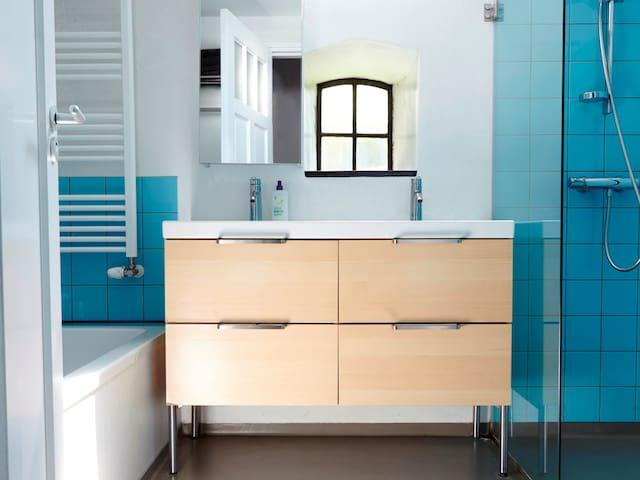 De grote badkamer met groot ligbad en dubbele douche