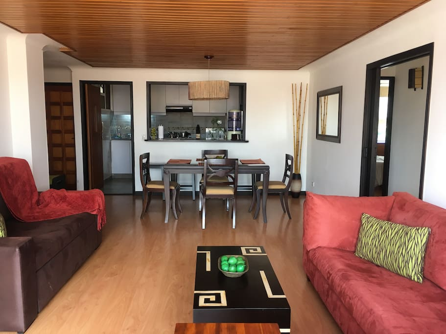 Another view of living and dining room with kitchen  in the background. Double sleeper sofa to your left for a 5th guest. The entrance to the apartment is to the far left.