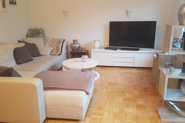 Großzügiges Wohnzimmer mit großem Fernseher und gemütlicher Sofaecke