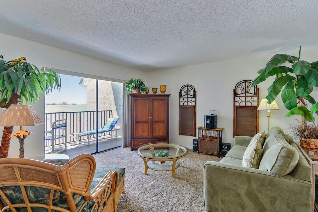 Carpeted living area, decorated in green and tan beach tones.