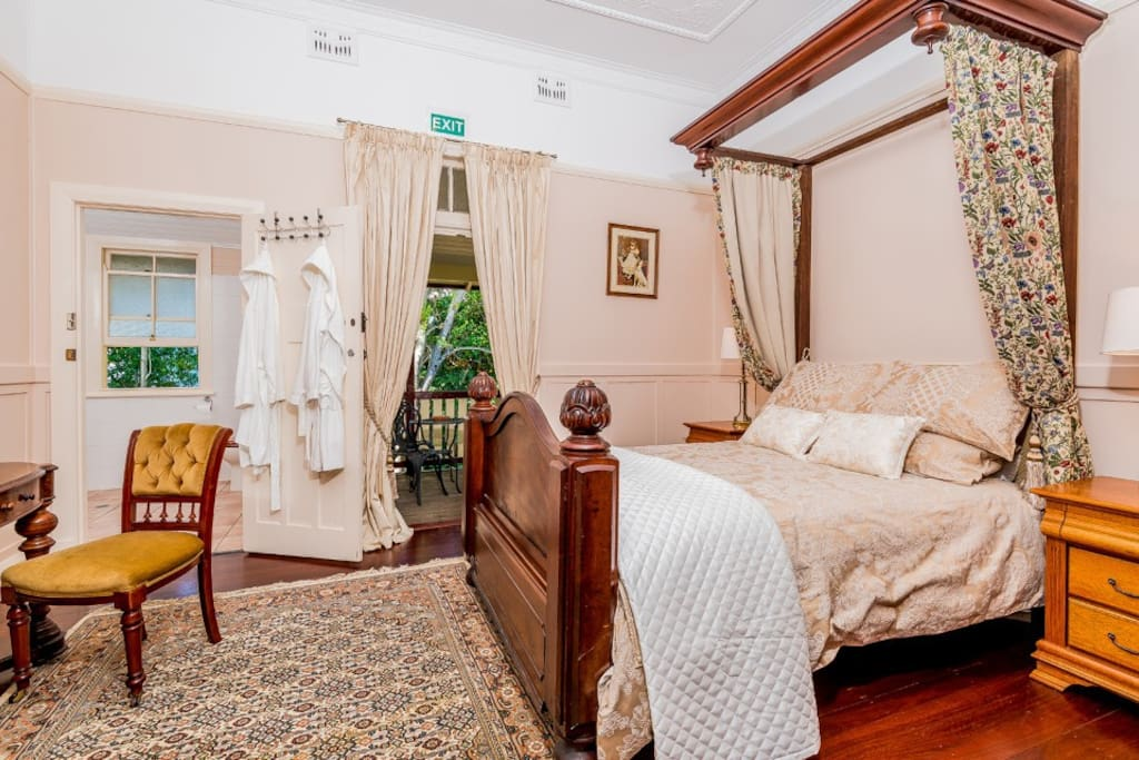 Main bedroom with ensuite, furnished with a beautiful queen size antique english walnut bed with half tester. The linens are Sheridan 1000 thread count for a comfortable sleep experience. Matching dressing  table and French doors that open to private verandah