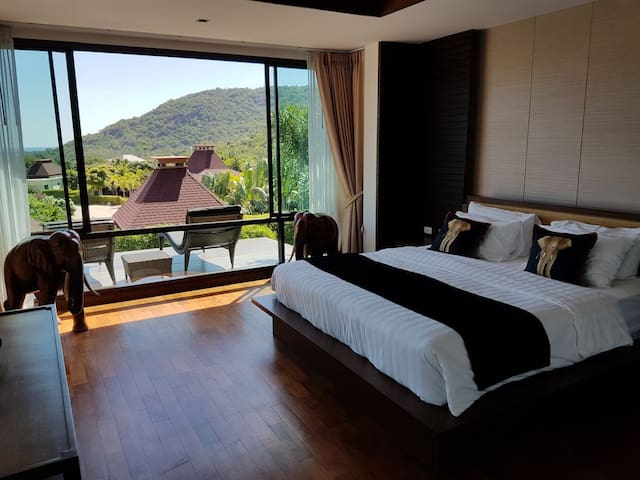Master bedroom with dark wooden floor and with panorama views