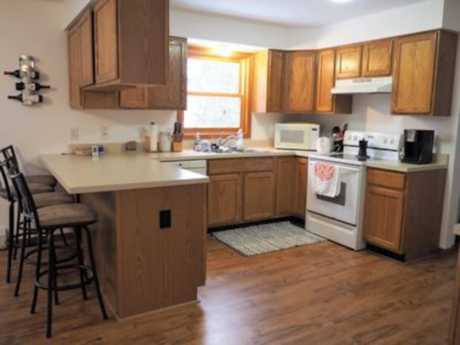 Fully equipped kitchen and breakfast bar with four stools.
