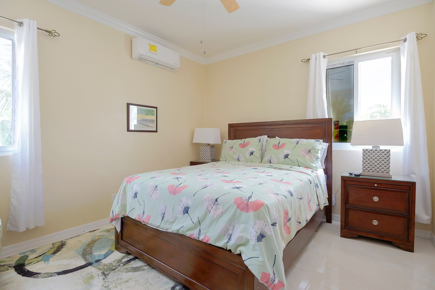 """This photo shows a spacious bright coloured bedroom, outfitted with one qeen size bed, two lamp stands, a 42"""" smart Television, a dress mirror and a clothes closet. The bedroom has a door which seperates it from the other areas of the apartment."""