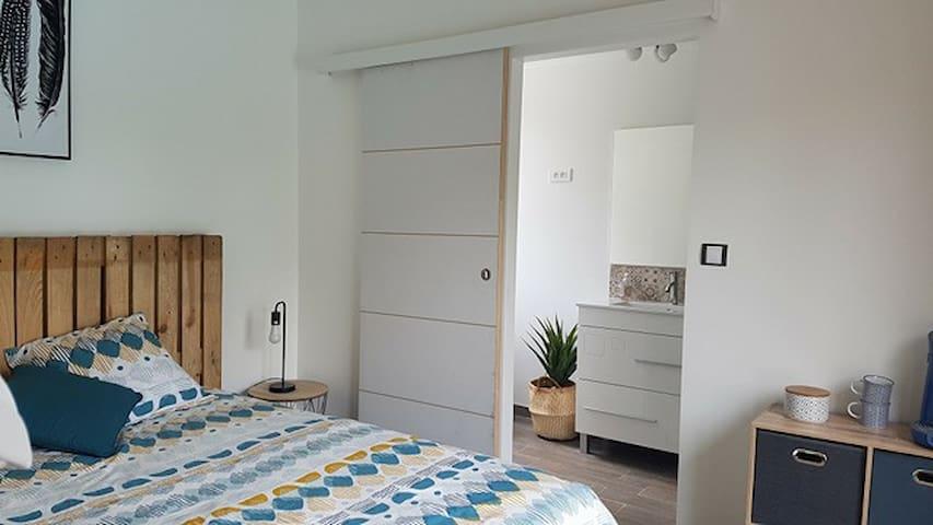 chambre avec accès à une salle d'eau, commode avec cafetière et bouilloire.
