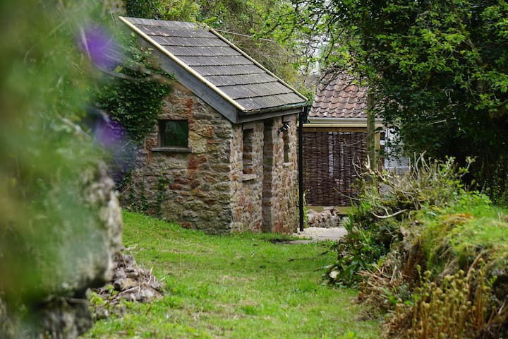 The Byre is a single room stone building. A few steps away is the spa bathroom and behind is the private breakfast patio