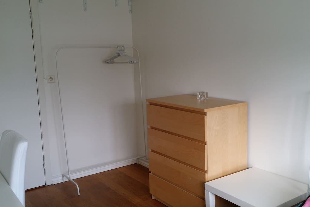 A drawer and cloth rack in the room