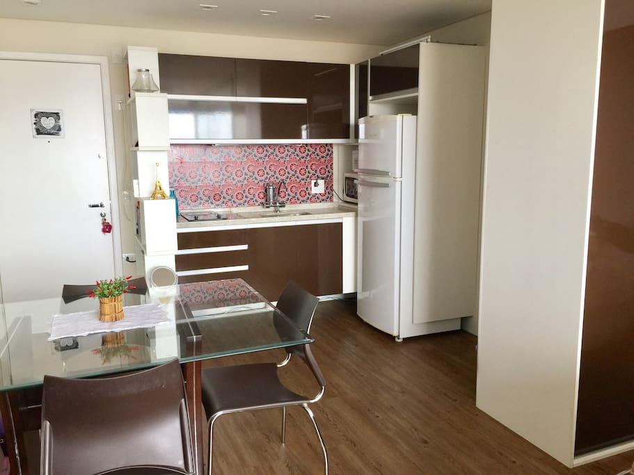 Cozinha toda equipada, com utensílios, cooktop, microondas, refrigerador, filtro de água e boa mesa para suas refeições.