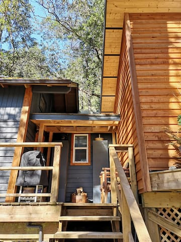 Arriving at Coppermoss Treetop, made up of 3 interconnected cottages, the living and kitchen area in one, and the bedroom and bathroom in the other two. A covered deck between is the perfect place to bbq.