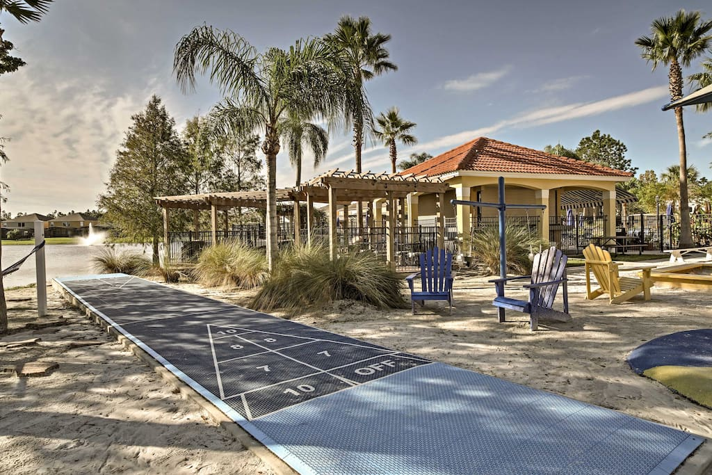The shuffleboard rests next to the playground and community pool.