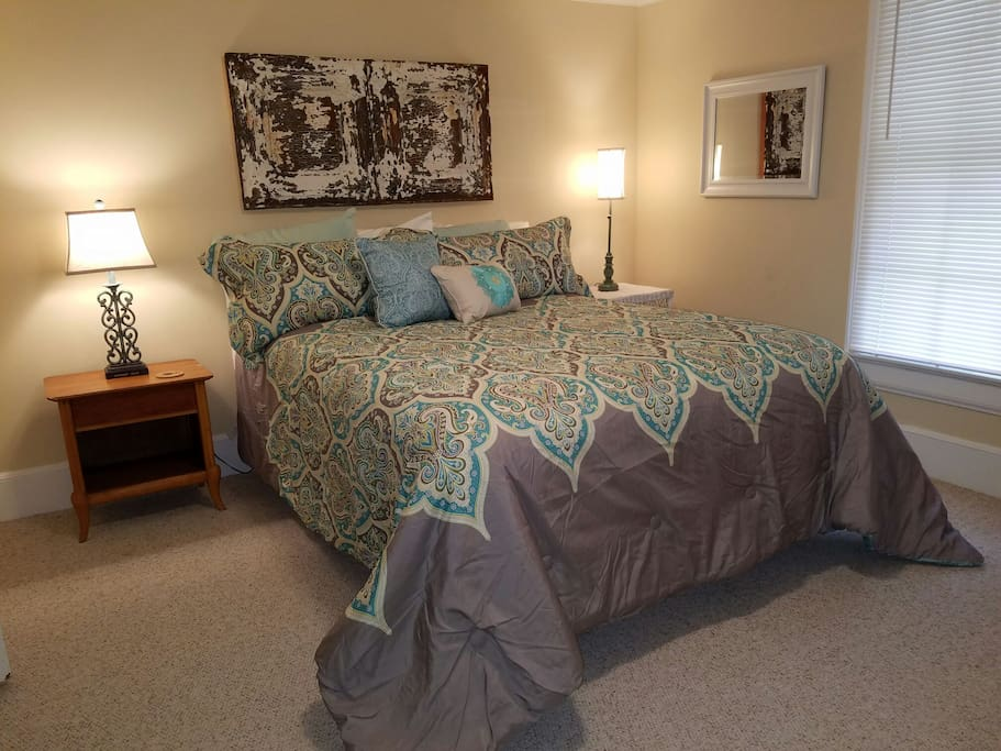 This bedroom features a queen bed, dresser, chest, baseboard heat and closet to hang clothes.