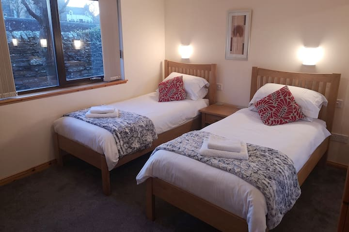 Twin bedroom includes large built-in wardrobe and desk with chair.