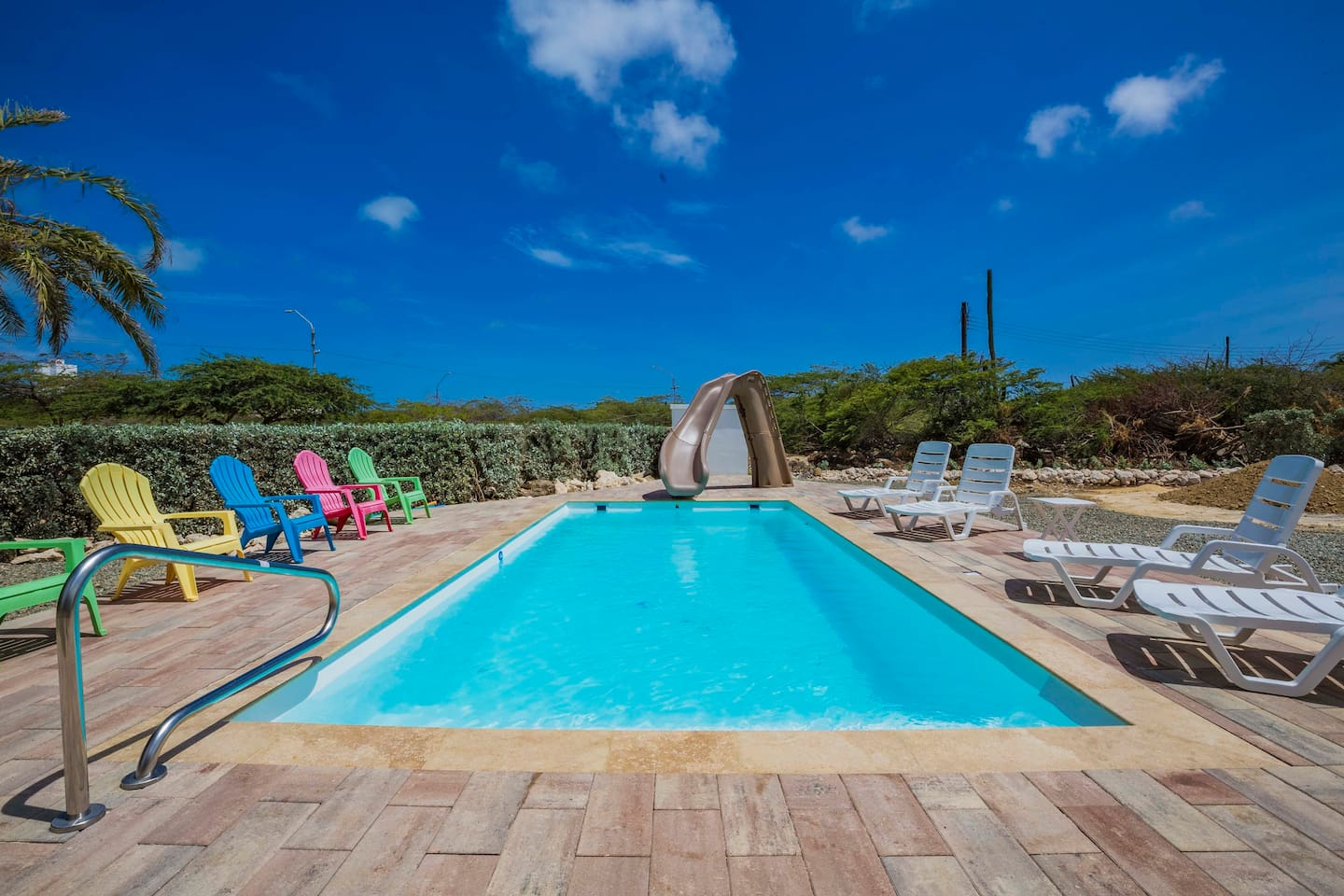Large Beautiful Pool under the Sun with great slide for adults and kids. Lounge Chairs and Colorful Chairs