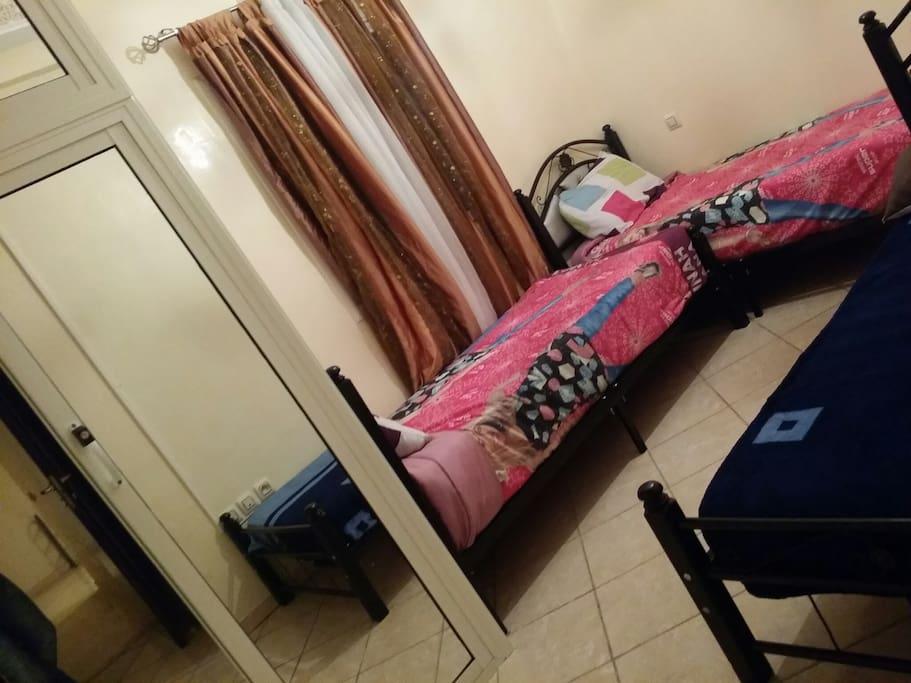 Une chambre pouvant accueillir plusieurs couchages avec des espaces de rangement et de vie