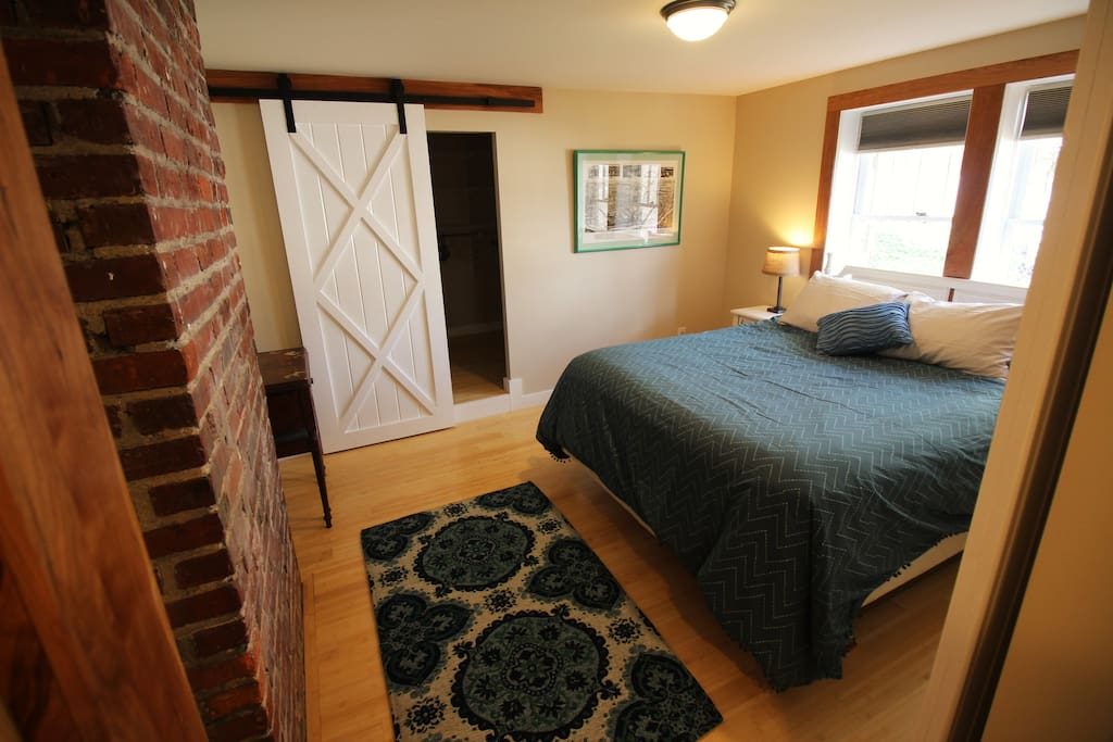 Bedroom has barn doors and exposed brick