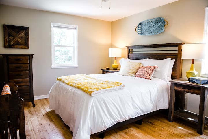 Main bedroom with queen bed and luxury linens on the upper level
