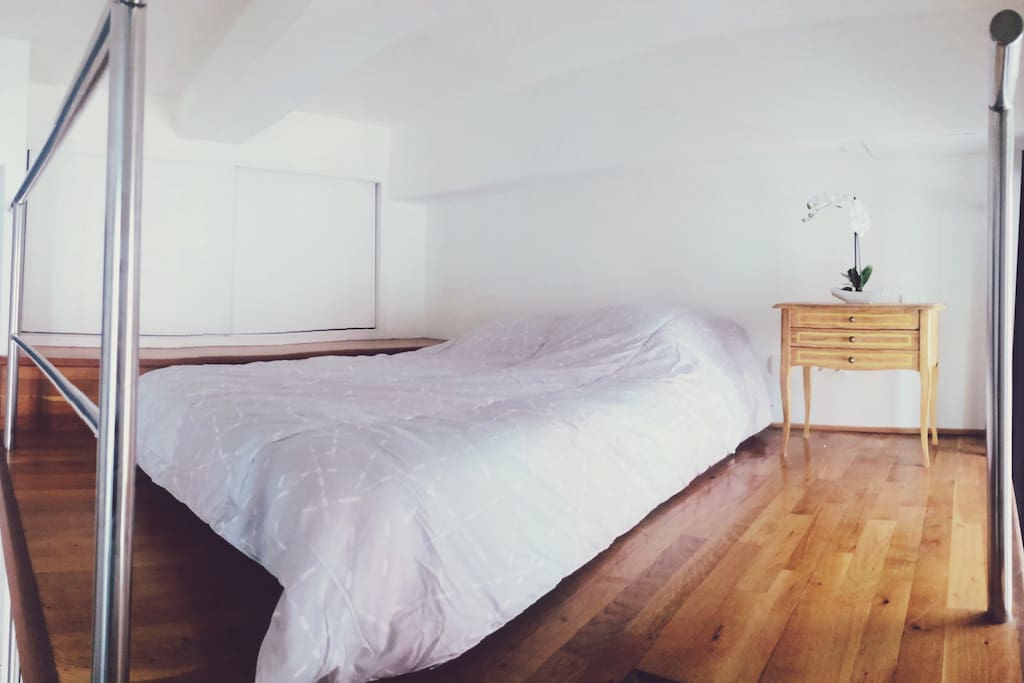 Mezzanine comportant un vrai lit 2 places et des rangements dans le meuble à gauche