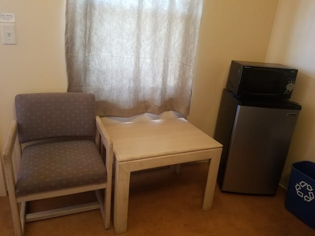 Each cabin style room also includes a microwave, mini-fridge, side table, and chair.