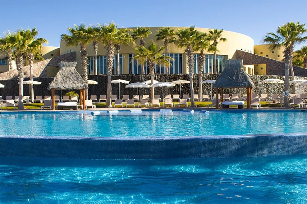 Lounge chairs and beds surround the outdoor pool.