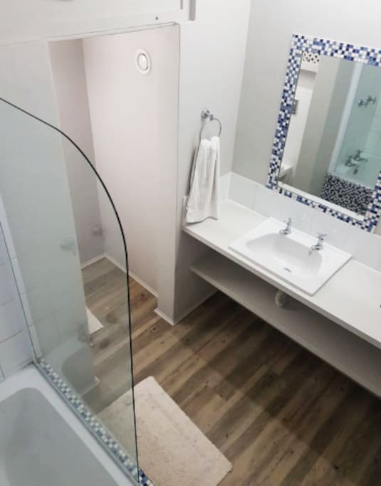 Contemporary simplicity bathroom for a good clean look - has a shower/bath combo, toilet, sink, and loads of counter space.