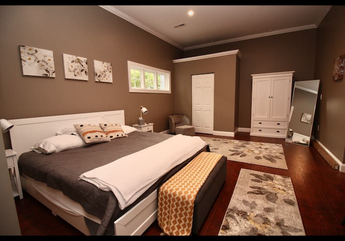 Spacious master bedroom with armoire and full length mirror.
