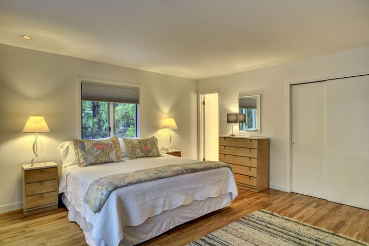 Large Master Suite features king bed, flat-screen TV,  newly renovated, private bathroom, and sliding glass door to pool area.