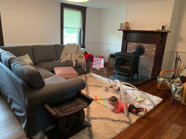 Cozy living room with a wood stove, Roku TV, large sectional sofa (cute baby not included)