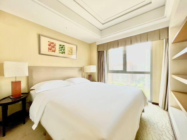 舒适的大床房,透亮的落地窗,整洁的置物架,伴随您的愉快旅程。