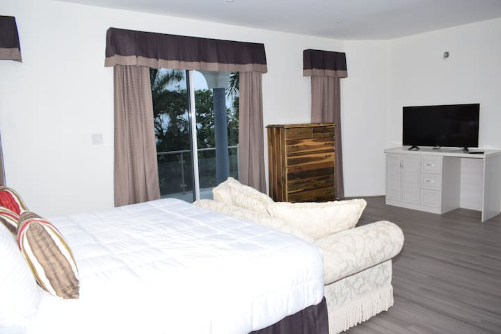 This picture shows king Suite No. 5 with private balcony on third floor overlooking saltwater pool and amazing view of the ocean