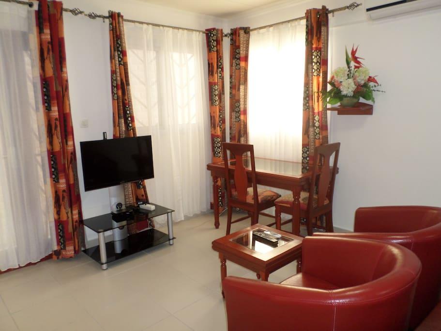 Le coin salon/salle à manger équipé d'une TV LED 32 pouces. L'abonnement aux chaînes câblées est pris en charge par la résidence.