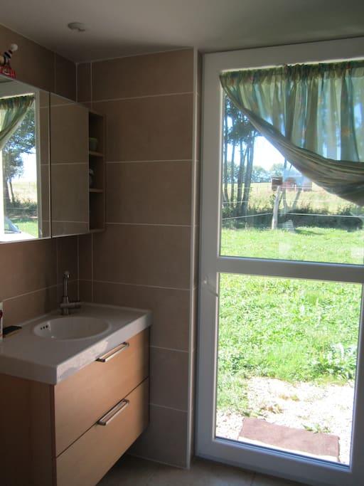 Salle de bain-chambre vue sur le parc chevaux.. porte donnant sur espace vert à disposition transat..