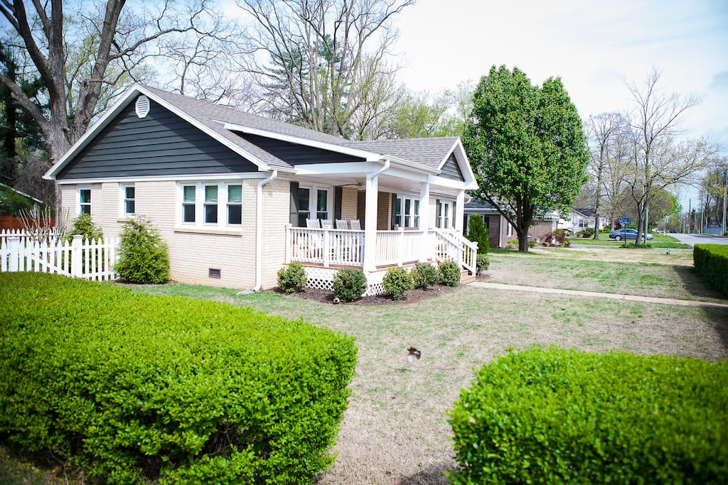 Spacious front porch, well-groomed boxwood hedge and classic cottage style
