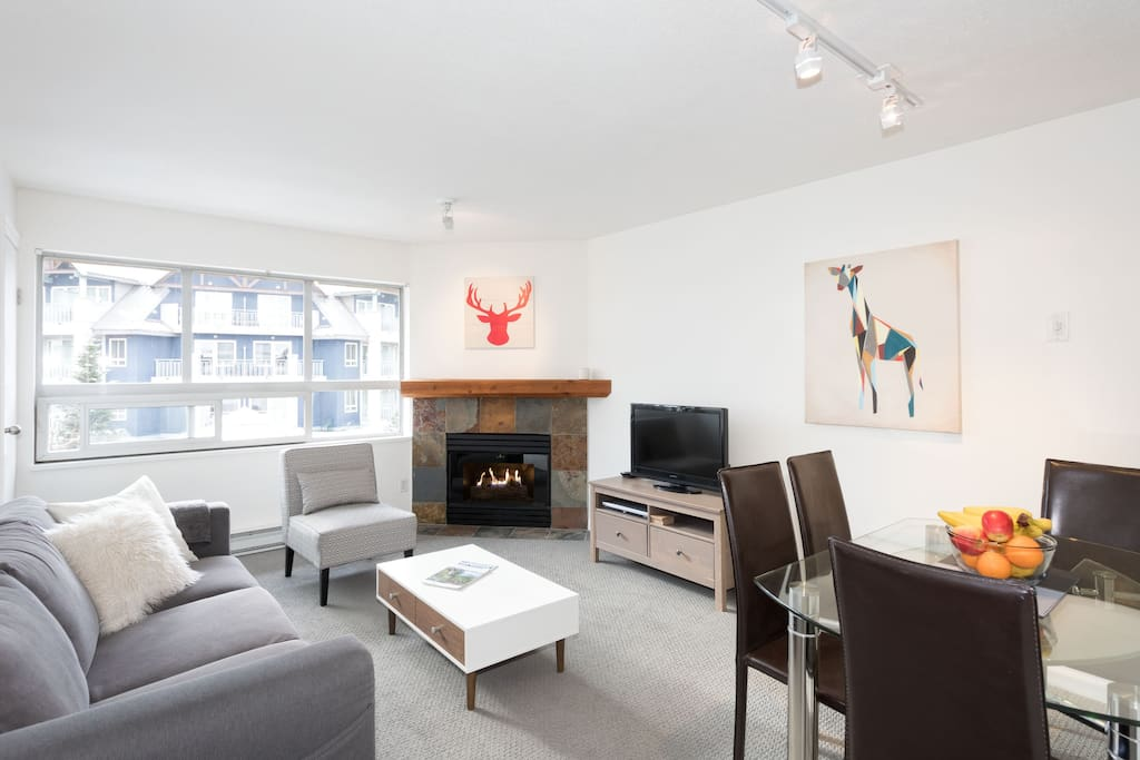 Bright living room with dining area and cozy gas fireplace.