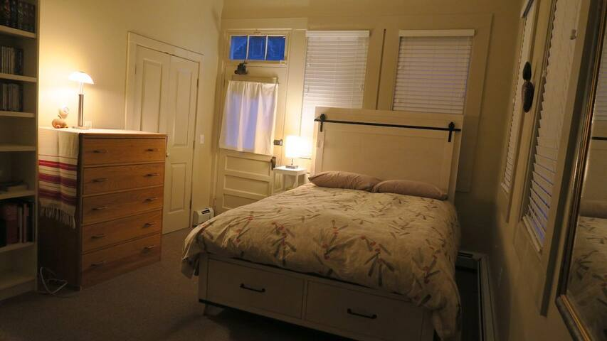 Queen-size bed with USB charging and phone holster in the headboard.