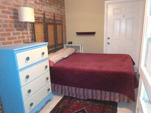 Full sized bed inside bedroom area. Door is for emergency exit.