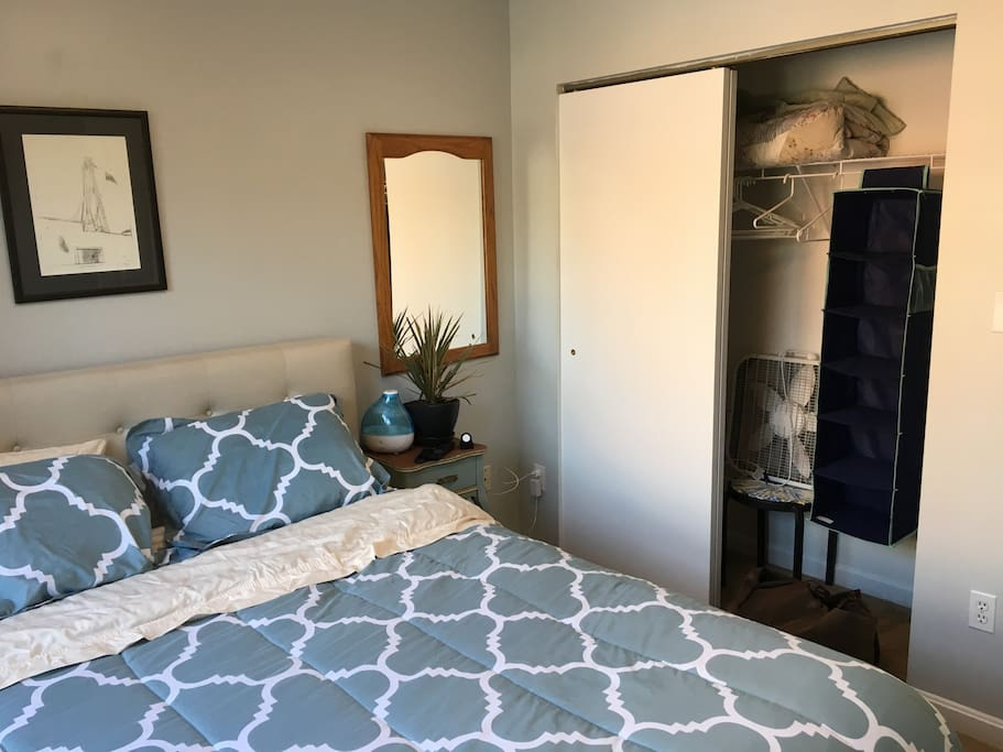 Private bedroom is furnished with a queen memory foam bed, shelf, extra bedding, ironing board, iron, side table, power strip & misc. toiletries.