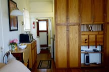 Good view of kitchenette and covered book case which has food and towels and desk